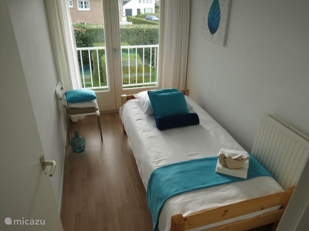 Slaapkamer met éénpersoonsbed en balkon aan zuidzijde