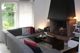 woonkamer met grote loungebank en open haard.