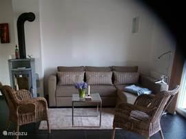 Zithoek woonkamer met tv nederlande zenders. Houtkachel en vloerverwarming en radiatoren