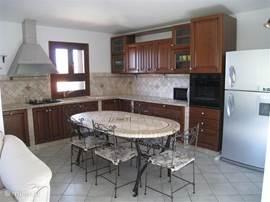 Ruime open keuken met diverse voorzieningen en toegang naar het balkon.