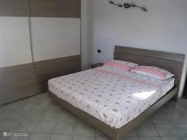 Ruime slaapkamer met 2-persoons bed, ruime kledingkast, 2 nachtkastjes en dressoir. Tevens toegang tot een balkon vanaf de slaapkamer.