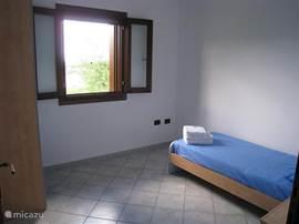 De derde slaapkamer met een 1-persoons bed, kledingkast en nachtkastje. Uitzicht vanuit het raam op de omgeving met bergen en natuur.