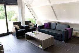 In de woonkamer staan twee fauteuils en een royale bank.