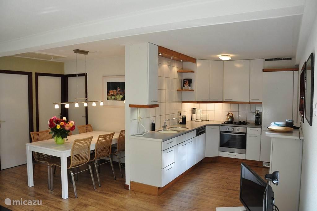 De eetkamer en open keuken gezien vanaf de zithoek. De keuken is voorzien van vaatwasser en hete lucht oven. Magnetron staat in bijkeuken.