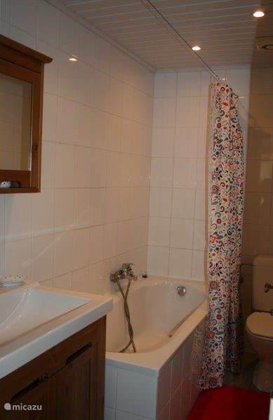 badkamer met bad, toilet en lavabo met kast