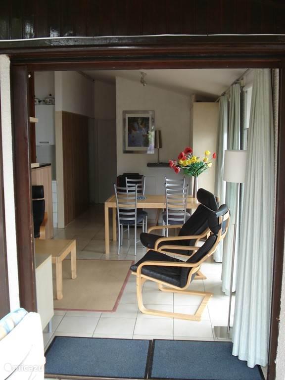 Het aanzicht van een deel van de woonkamer, de open keuken en de gang naar de slaapkamers en de badkamer. De woonkamer heeft een televisie met video-speler, een dvd-speler, boeken, films en bordspellen.