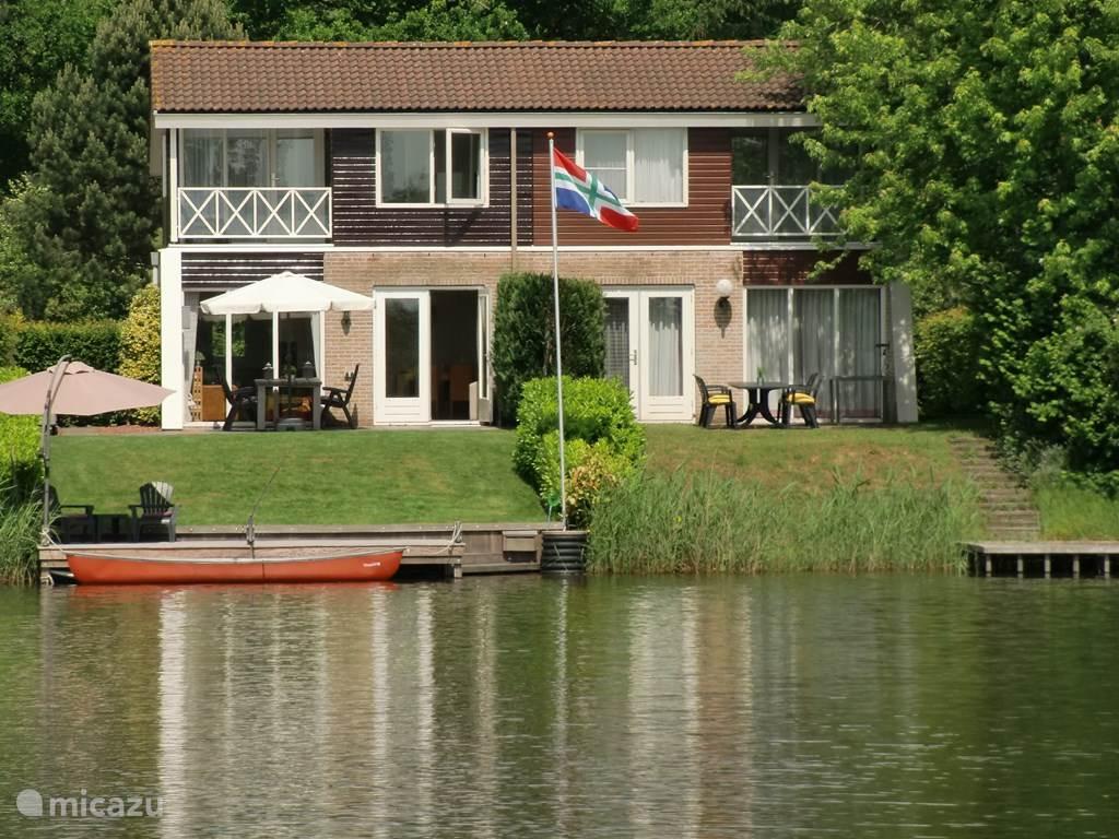 De achterzijde van de vakantiewoning direct aan het meer gelegen. Een steiger bijna over de volle breedte van de tuin