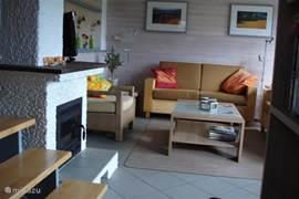 Comfortabele woonkamer met fauteuil en twee 2p zitbanken (1 bank niet zichtbaar op de foto)