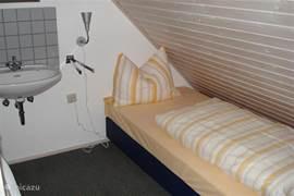 2e slaapkamer2e verdieping met apart staande boxspringbedden met ook openstaande deur naar balkon en ook een wastafel.
