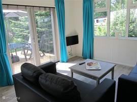 Gezellige woonkamer met twee 2,5-zitsbankjes, grote salontafel en 2 kleine salontafeltjes.