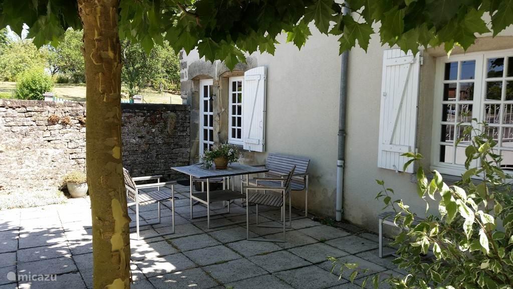 Terras op de binnenplaats onder de platanen voor Le Pigeonnier met twee tuinstoelen houten tafel en bankje.