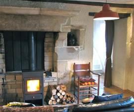 Huiskamer met fijne houthaard en doorgang naar keuken.