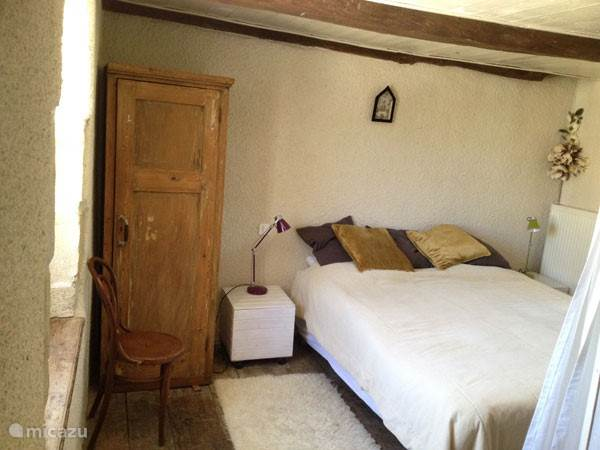 Romantische slaapkamer op de eerste verdieping met hotel bedden, ruim in de kussens, met een klein raam met uitzicht op de tuin en een openslaand raam (met luiken) naar de binnenplaats.