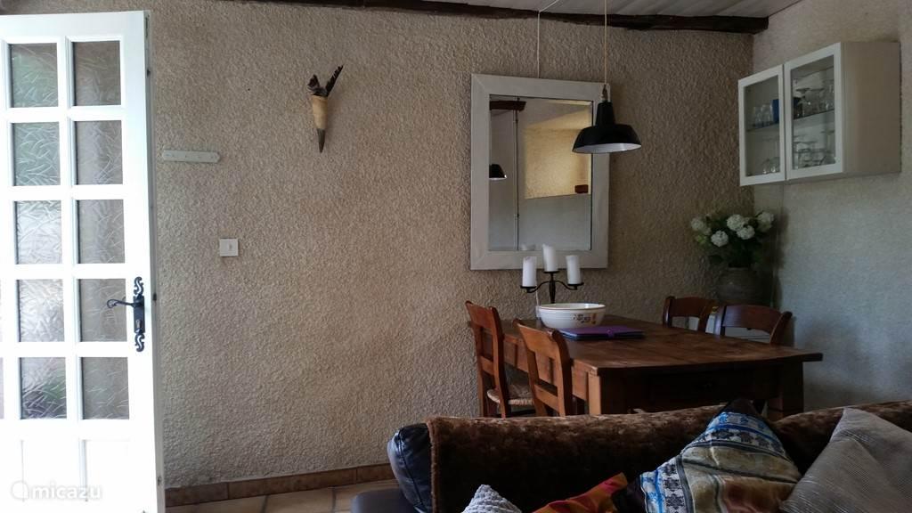 Huiskamer met houten tafel en loungebank, deur en openslaande ramen naar de binnenplaats en raamlicht naar tuinkant.