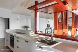 Prachtige keuken met volop werkruimte en alle voorzieningen. Heerlijke bar naar de veranda met buiteneethoek.