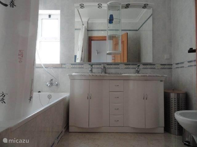 De badkamer met ligbad.