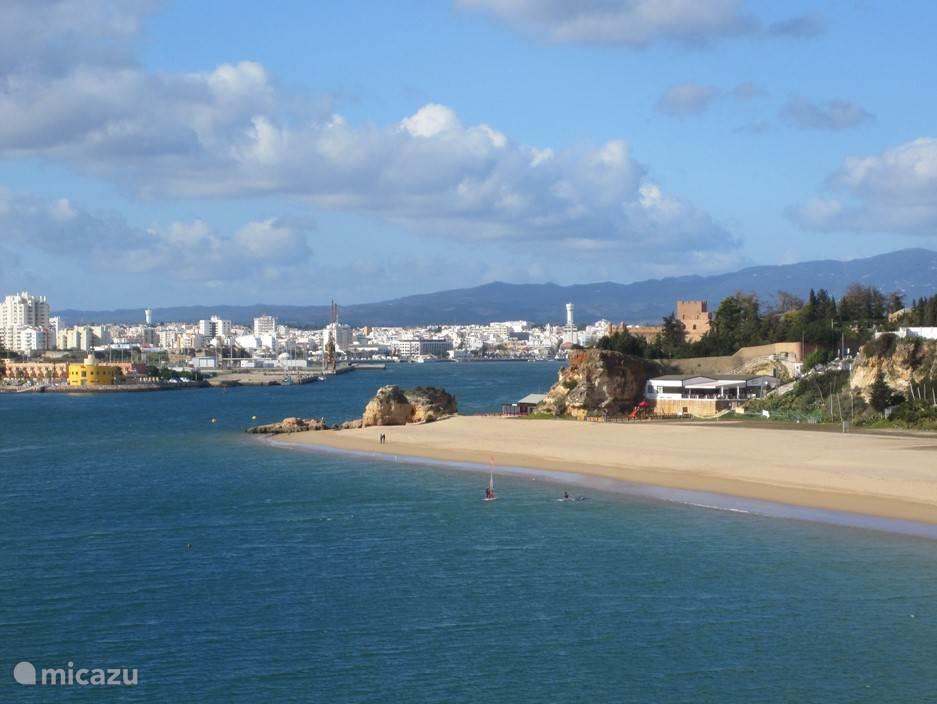 Het strand van Ferragudo, met op de achtergrond de monding van de rivier de Arade (die naar Silves stroomt) en de witte bebouwing van Portimão. En dat op een kwartiertje rijden van Casa Castelo!