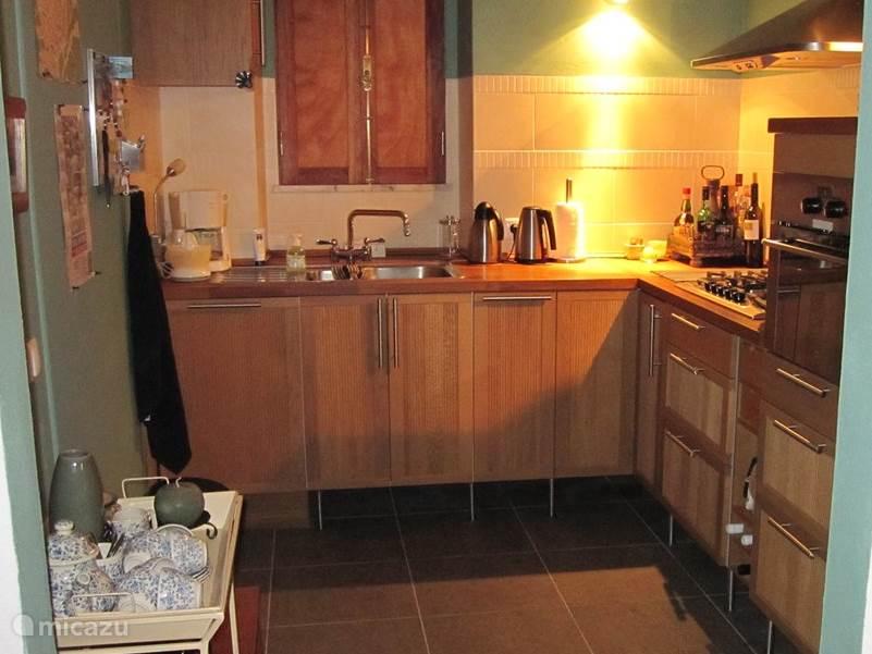 Een ruime keuken om heerlijk in te koken. Op de vloer liggen grote tegels van Portugees natuursteen in een mooie kleur: verde (=groen).