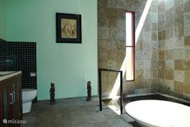 The large bathroom with round bathtub Terazo surrounded by a fish pond. The rain shower shower made for a refreshing at the end of a tropical day.
