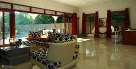 the living room with sofa and lounge overlooking the tropical garden
