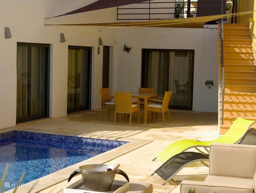 Het vooraanzicht van het appartement met het verkoelende zwembad en terras.Ook zijn er ligstoelen met parasols op het terras om lekker te luieren.