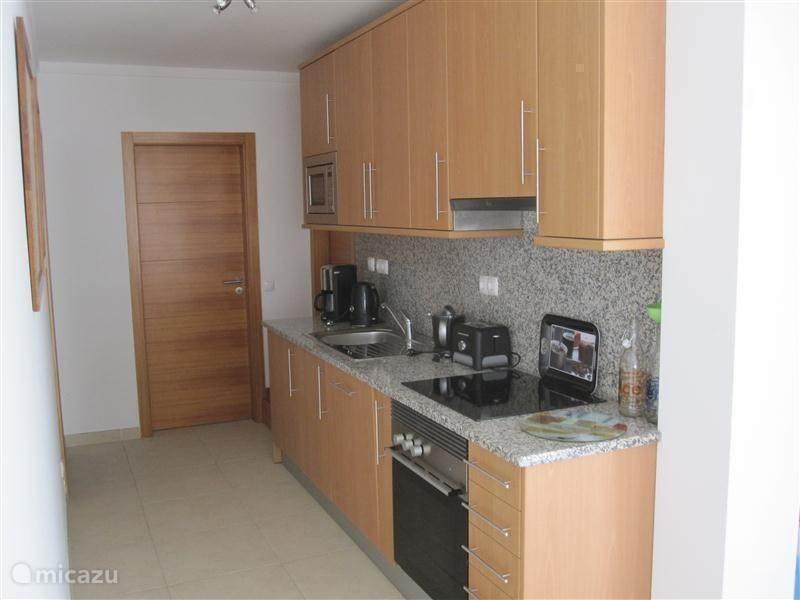 Keuken met oven en afwasmachine. In aparte ruimte een wasmachine aanwezig.