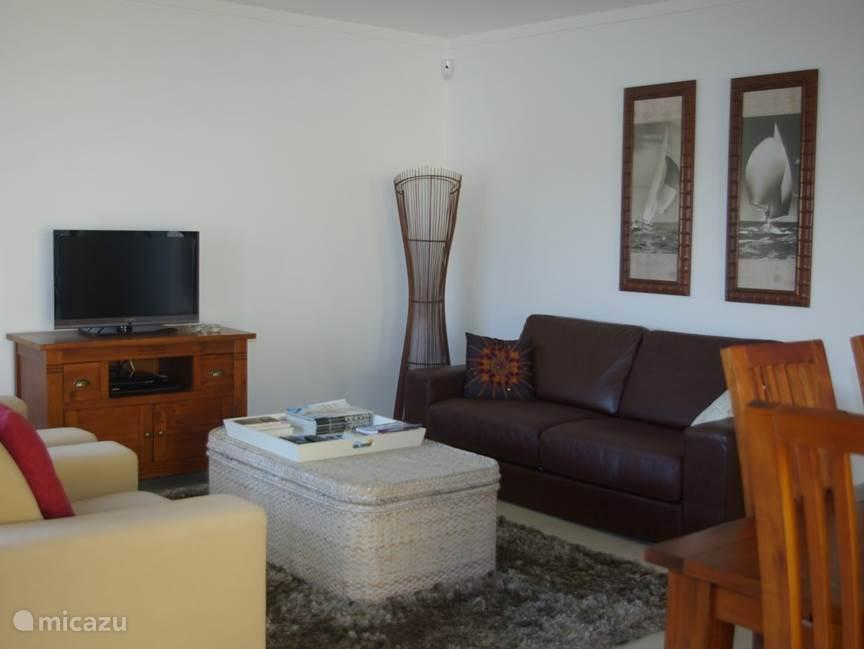 De woon-slaapkamer met bedbank en 2 luxe fauteuils. Een tv en eettafel aanwezig.