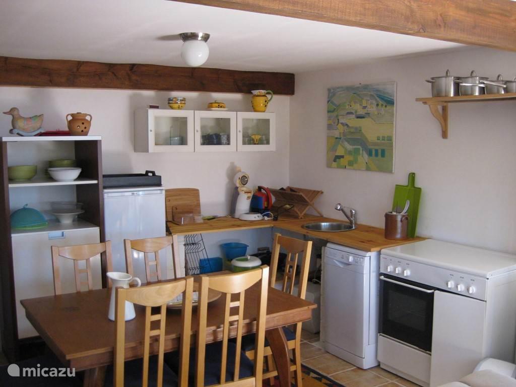 De keukenhoek met vaatwasser, fornuis, koelkast en vrieskast.