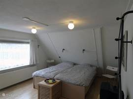 Slaapkamer 1 is gelegen op de eerste verdieping van vakantiewoning Afterdaan, heeft twee eenpersoons bedden en een ruime kast. Deur naar dakterras. TV aanwezig.