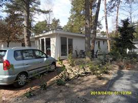 Bij het huisje is een ruime parkeerplaats. U kunt hier ook zien, dat u wel in het bos zit, maar niet in de volle schaduw.