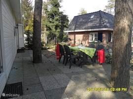 Een ruim terras met een leuk tuinzitje en voldoende ruimte om in- of uit de zon te zitten.