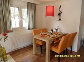 De gezellige huiskamer heeft een stevige tafel met leuk gekleurde stoelen