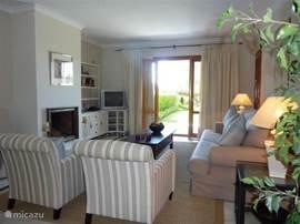 De heerlijk lichte woonkamer met openhaard en openslaande deuren naar terras en tuin.