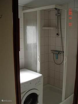 Douche met voldoende opbergruimte en een wasmachine.