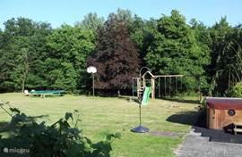 Overzicht tuin met speeltoestellen en jacuzzi