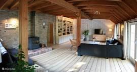 Woonkamer met houtkachel, gevulde boekenkast en openslaande deuren naar het terras aan de zuidzijde