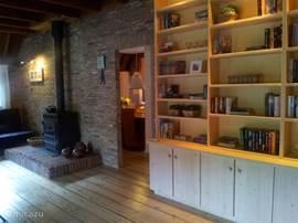 Woonkamer met houtkachel en doorkijkje naar eetkeuken