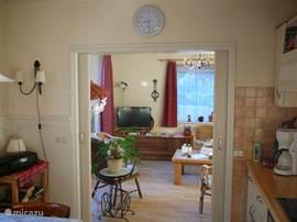 De knusse woonkamer en de keuken, kunnen via een schuifdeur van elkaar gescheiden worden