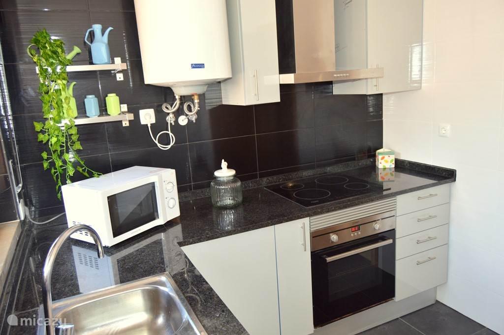 Keuken, met wasmachine, afwasmachine, koffiezetapparaat en nog veel meer.