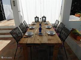 Overdekt terras waar heerlijk ontbeten kan worden, maar ook lekker eten in de avond. Lange houten tafel met 6 tuinstoelen en kussens.