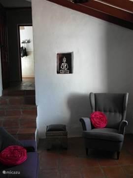 De woonkamer heeft een ruime bank en twee fauteuils. Twee ottomans om je voeten op te leggen of om als kruk te gebruiken.