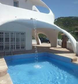 Het zwembad met een kleine waterval vanaf het dak...heerlijk genieten in een prachtige omgeving.