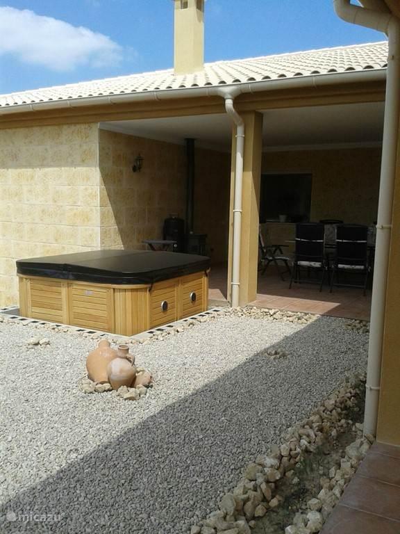 Hier ziet u de besloten overdekte patio met een moderne jacuzzi