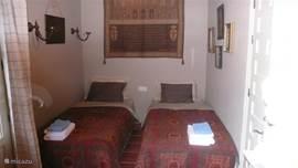 De tweede slaapkamer met openslaande deuren naar het zwembad.
