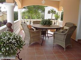 De veranda is een heerlijke plek om te genieten van het uitzicht op de uitloper van de Montgo, het zwembad en de tuin. Rondom de tafel staan comfortabele stoelen.