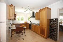 Ruime (eet)-keuken met vaatwasser, elektrische 4-plaats kookplaat, oven, koelkast met vriesvak; aangrenzende bijkeuken met wasmachine en droger.