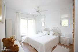 Ruime tweepersoons slaapkamer met ingebouwde kast en schuifpui naar groot zonnebalkon. De 2 slaapkamers op de 1e verdieping zijn ieder voorzien van airconditioning en plafondventilator