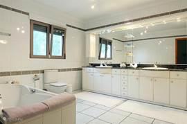 Zeer grote badkamer met dubbele wastafel, ligbad en toilet behorend tot de masterbedroom.