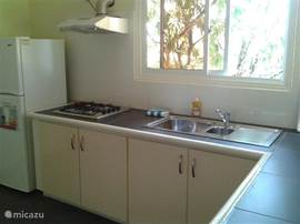 Large L-shaped kitchen, 4 burner gas cooker, fridge / freezer.