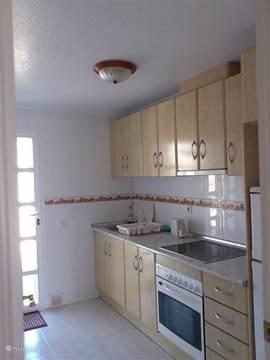 Keuken met afzuigkap, koelkast met vriesvak en oven.